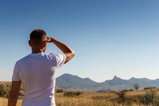 A man looking into the distance to the mountains
