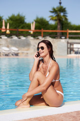 Sensual and sexy woman standing in swimming pool and talking to mobile