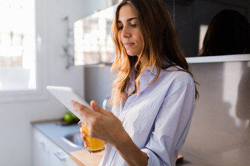 Woman holding digital device and drinking orange juice at home