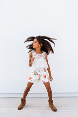 A cute African American girl jumping up against a white background