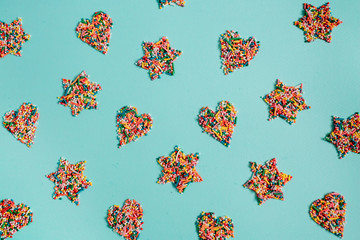 Colorful heart and stars made of confetti on blue background. Flat lay, top view.