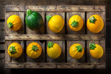 Yellow zucchini overhead group lined up on old rustic wooden box and dark background in studio
