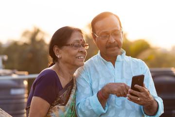 Happy senior couple browsing on smartphone
