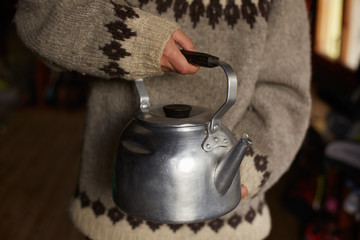 Close up of hands holding an old aluminum kettle of someone wearing a thick wool sweater