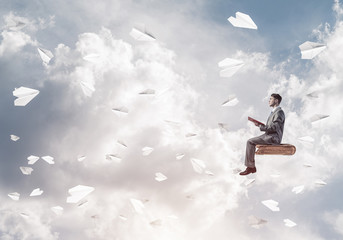 Businessman or student reading book and paper planes flying arou