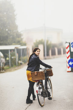 WOman with braided hair turn towards the camera while walking and pushing a bike