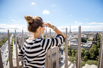 Young woman tourist enjoying great cityscape view on Paris during the sunny weather in France. Image focused on the background woman is out of focus