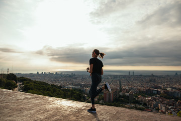 Fit woman running above city at sunrise.