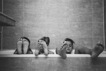 Siblings having bath at home.