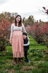 Pregnant Asian woman with her son outdoor in a park