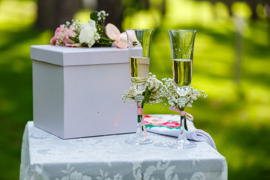 Two wineglasses with pink ribbon and gift box on a table on wedding ceremony