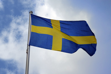 Flag of Sweden with a yellow cross on a blue background, national symbol or sign of the european country, fluttering in the wind against the blue sky with clouds on a sunny day