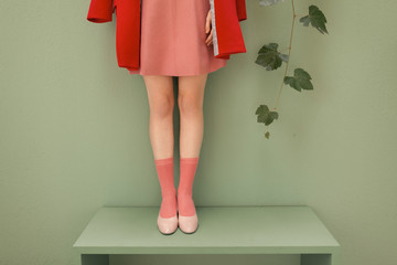 woman with red and pink clothes in front of a green wall