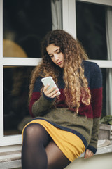 Curly woman reading from mobile phone