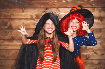 funny children sister twins girl in witch costume in halloween.