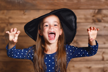funny child girl in witch costume in halloween.