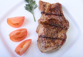 grilled pork chop with vegetable on plate on wooden board