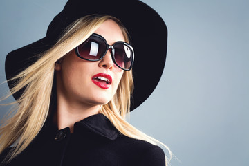 Beautiful young blonde woman in a black coat, hat and sanglasses