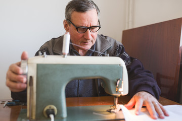 Elder man sewing a piece of cloth with sewing machine