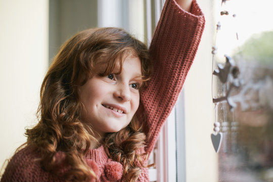 Close up of happy little girl holding a christmas ornament by the window