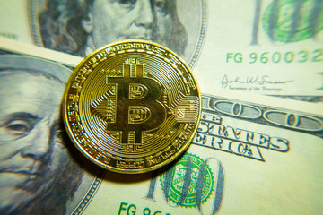Golden bitcoin coin on the one hundred dollars banknote. Macro. Cryptocurrency concept