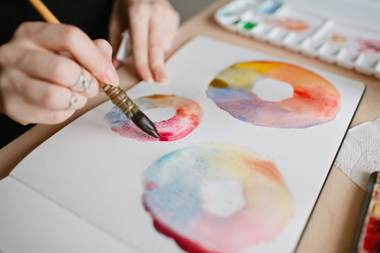 Girl artist paints watercolors color wheel