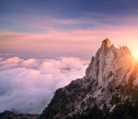 Mountain landscape at sunset. Amazing view from mountain peak on the high rocks, blue sky, pink clouds and in the evening. Low clouds. Colorful nature background. Adventure. Travel in Crimea. Cliffs