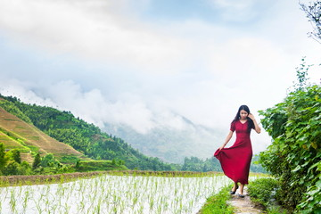 Girl in red dress walking by the rice terrace
