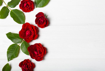 Red roses and green leaves on a white wooden table. Vintage floral pattern. View from above. Flower pattern. Empty space for text