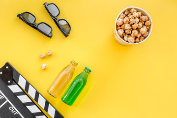 Snacks for film watching. Popcorn and soda near clapperboard, glasses on yellow background top view copyspace