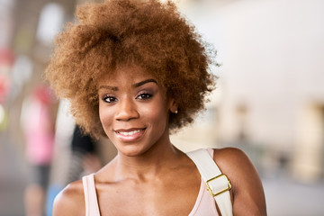 portrait of happy african american woman at airport ready to depart for flight