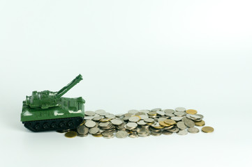 Green toy tank crossing over stack of coins isolated on white background, concept of expense and cost of war.