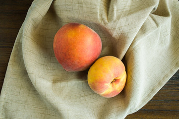 2 peaches on a beige napkin viewed from above