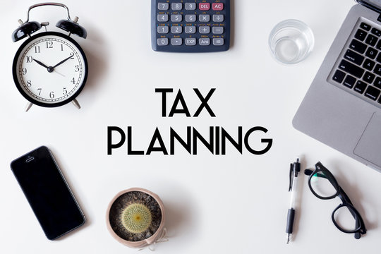 Tax Planning words written on white table with clock, smartphone, calculator, pen, cactus, glass and laptop