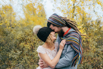 Bride in a knitted hat with a pom pom, hat covering her eyes. Groom in a colorful scarf. Happy young newlywed couple touching foreheads and noses in park