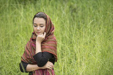 Portrait of happy young muslim woman over blurred the green field background