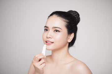Asian woman applying hygienic lip balm over grey background