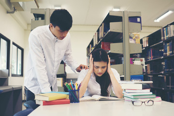 Portrait of student touching head while reading book in college library. Education concept.