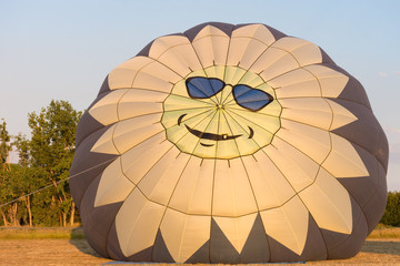 A hot air balloon being inflated in the golden light of sunrise. The top of the balloon has a stylized yellow sun with a face and rays that is wearing blue sunglasses.
