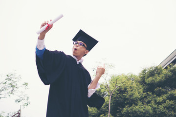 Happy graduate student holding a diploma in hand. Education concept.