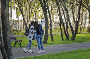 Girls making selfie in the Warriors-Winners Park in Lefortovo neighborhood of Moscow city.
