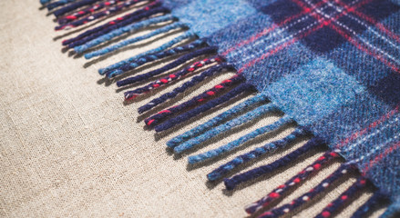 Country woolen fabric. Fringe of an old Scottish warm blanket