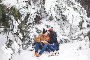 Сouple having fun and throwing snow in winter forest. A lot of snow around