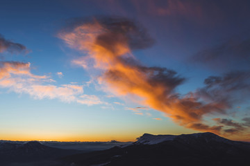 Amazing colorful sunset high in mountains. Orange clouds and blue sky
