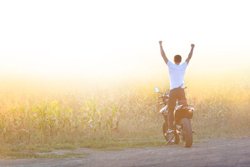The motorcyclist is holding his hands up at the sunrise. Feeling of freedom.. Wall mural