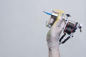 Tattoo machine on tattoo artist hand on white background