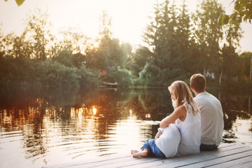 Family sitting near water and watching the lake at sunset