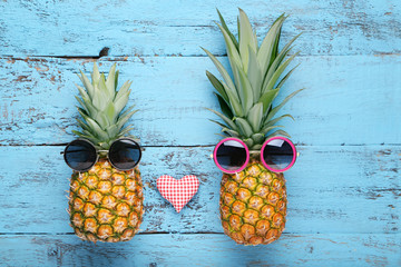 Ripe pineapples with sunglasses on blue wooden table
