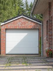 Gemauerte Garage mit einen weißen Tor