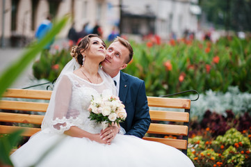 Elegant wedding couple sitting on a bench in the park and looking at each other's eyes.